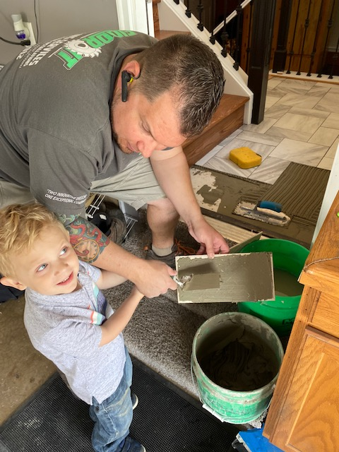 Little boy helping mix the paint.